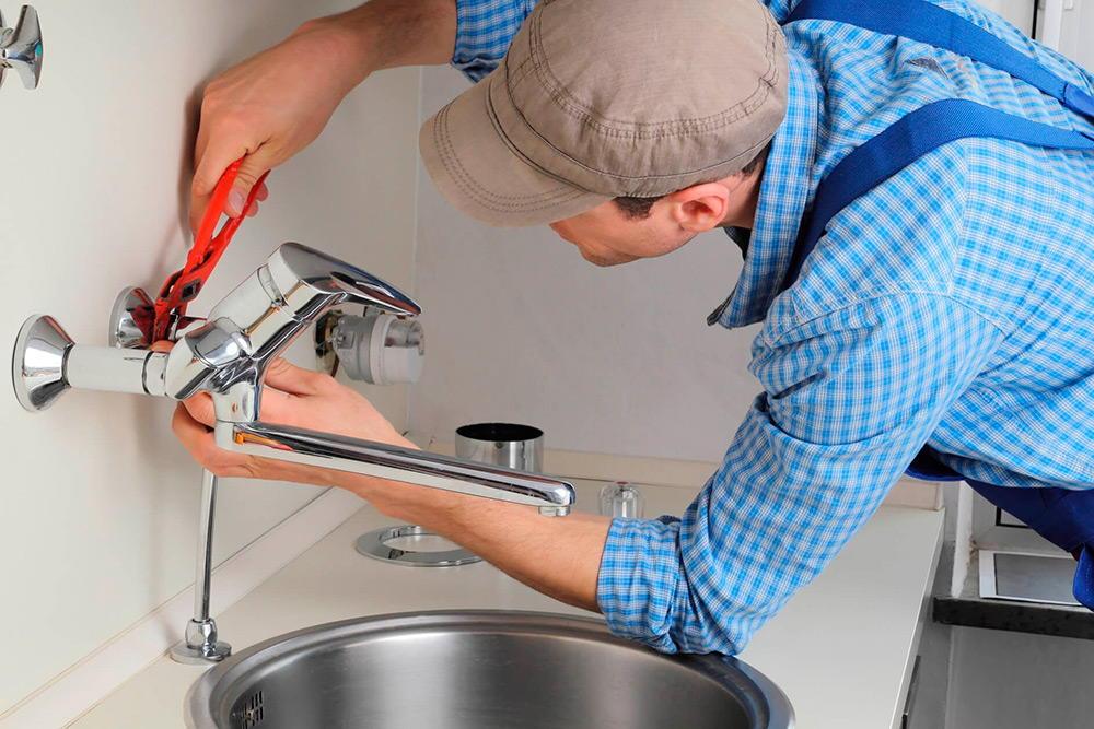 Мужчина ремонтирует кран на кухне фото